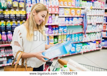 Smiling woman walking with trolley at supermarket