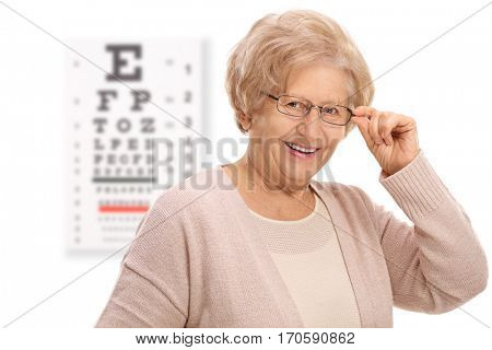 Mature woman smiling in front of an eye chart isolated on white background