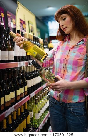Woman hesitating between two bottles of wine in supermarket