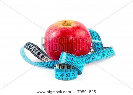 Red ripe fresh apple and measuring tape as part of a useful relationship to health