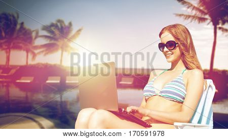 summer holidays, vacation, technology, people and internet - happy young woman in shades with laptop computer on beach