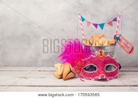 Purim holiday concept with hamantaschen cookies or hamans ears in bucket and carnival mask over rustic background