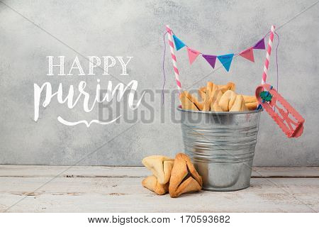 Purim holiday greeting card with hamantaschen cookies over rustic background