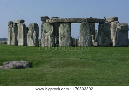Horizontal image of Stonehenge England with green grass and blue skies.