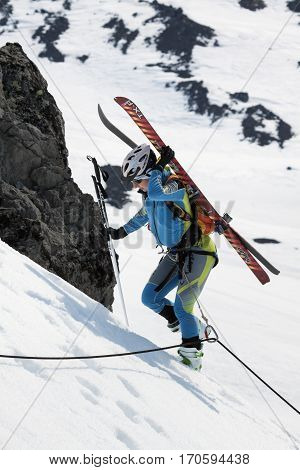 AVACHA VOLCANO KAMCHATKA PENINSULA RUSSIA - APR 21 2012: Open Cup of Russia on Ski Mountaineering on Kamchatka - young woman ski mountaineer climbing on rope on rock with skis strapped to backpack