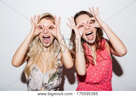 Portrait of two smiling women looking at camera through fingers isolated on a white background