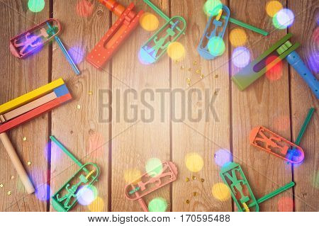 Purim holiday concept with noisemakers and bokeh lights on wooden background. Top view from above