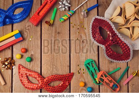 Purim holiday concept celebration with carnival mask on wooden background. Top view from above