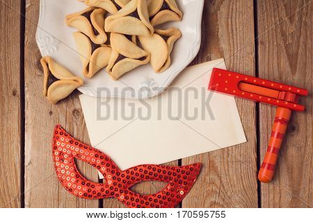 Purim holiday concept with greeting card hamantaschen cookies and carnival mask on wooden background. Top view from above