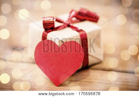 love, date, romance, valentines day and holidays concept - close up of gift box and blank red heart-shaped note on wood (vintage effect)