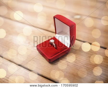 proposal, engagement, valentines day and holidays concept - close up of red gift box with diamond engagement ring on wood (vintage effect)