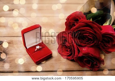 love, proposal, valentines day and holidays concept - close up of gift box with diamond engagement ring and red roses on wood over lights background (vintage effect)