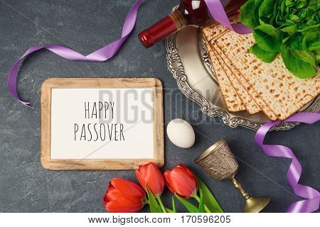 Passover holiday concept seder plate matzoh and photo frame on dark background. Top view from above
