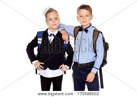 Two happy schoolchildren posing together at studio. School uniform. Educational concept. Isolated over white.