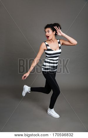 Full length of scared african american young woman running away over grey background