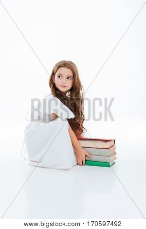 Pretty little girl sitting and taking stack of books over white background