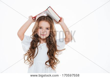 Pretty curly little girl standing and holding book above her head over white background