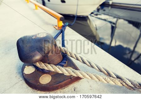 sailing, safety, mooring and water transport concept - rusted iron mooring bollard with rope on concrete pier