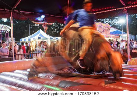 LAWRENCEVILLE, GA - SEPTEMBER 2016:  A composite of two images shows motion blur of man holding on while riding a mechanical bull at the Gwinnett County Fair in Lawrenceville GA on September 17 2016.