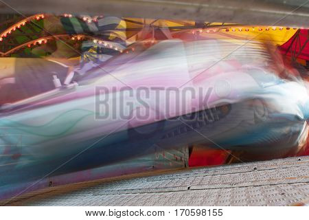 Composite shows motion blur of people riding fast carnival ride