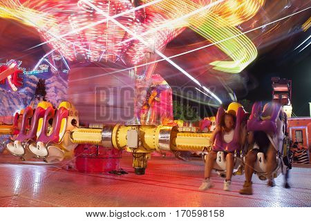 LAWRENCEVILLE, GA - SEPTEMBER 2016:  A composite of two images shows motion blur of fast-moving carnival ride at the Gwinnett County Fair in Lawrenceville GA on September 17 2016.