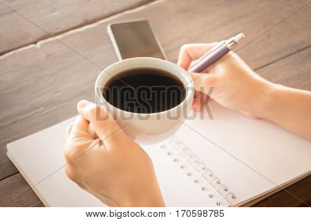 Hand on coffee cup and writing stock photo