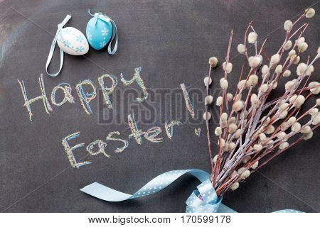 Colorful easter eggs and pussy willow over blackboard with  greetings