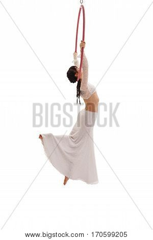 Young girl in white lace skirt and top hanging on a hoop and streching gracefully in studio