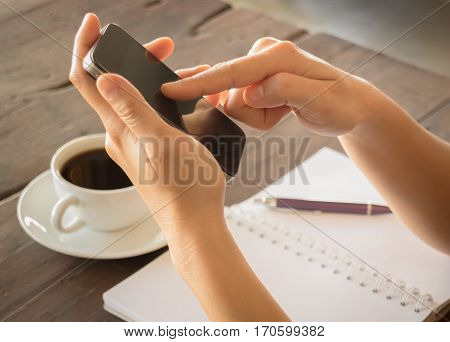 Hand on smartphone at coffee shop stock photo