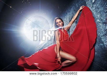 Stunning beautiful brunette posing against moonlight
