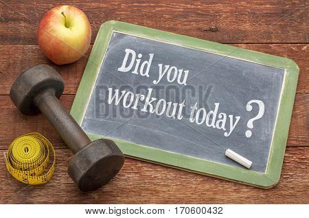 Did you workout today? A slate blackboard sign against weathered red painted barn wood with a dumbbell, apple and tape measure