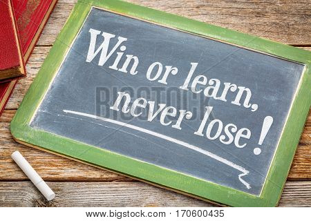 Win or learn, never loose - inspirational text on a slate blackboard with a white chalk and a stack of books against rustic wooden table