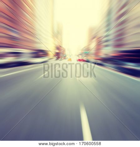 Motion blurred image of empty urban road. Vintage style.