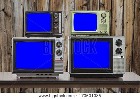 Four vintage televisions with old wood wall and chroma key blue screens.