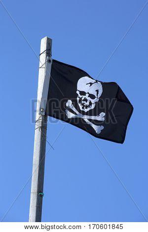 Pirate flag also named Jolly Roger.  Black flag on blue sky.