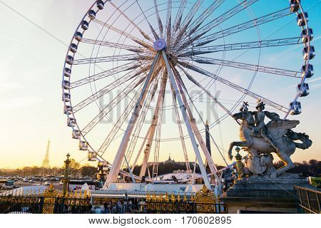 PARIS, FRANCE - CIRCA DECEMBER 2016: The ferris wheel on Concorde square as seen from the Tuileries Garden, Eiffel Tower in the background.