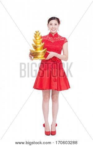 young asian woman in red cheongsam holds gold ingot in chinese new year