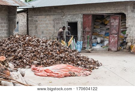 Zanzibar, Tanzania - July 14, 2016: Local men of Zanzibar putting stuff into their shacks, trash everywhere, dirty-looking street