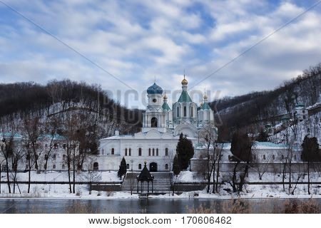 Assumption Cathedral and Church of the Intercession of Sviatohirsk Lavra. Cloudy day in February. On the waterfront
