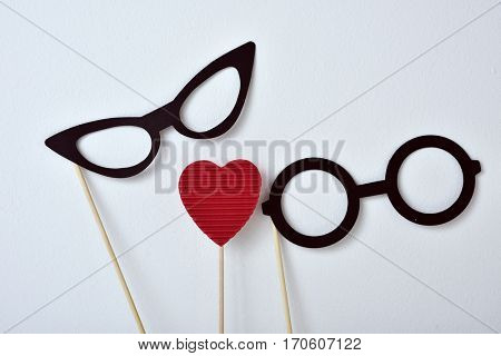 a pair of glasses for women, a pair of glasses for men and a red heart attached to sticks, against an off-white background