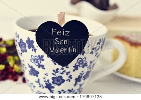 closeup of a heart-shaped signboard with the text feliz san valentin, happy valentines day written in spanish, in a cup of coffee, on a table set for breakfast