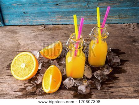 Summer refreshing drink or juice from a ripe orange in glass bottles next to the ice cubes and slices of orange on color wooden background.The horizontal frame. Place for text
