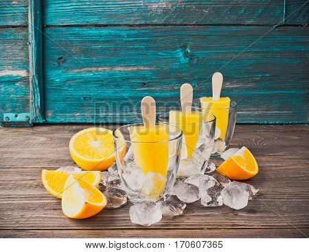 Summer Popsicles or orange juice frozen on a stick in glass glasses adorned with ice cubes and slices of ripe orange on a dark wooden background. Front view.The horizontal frame. Place for text.