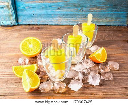 Summer Popsicles or orange juice frozen on a stick in glass cups decorated with ice cubes and slices of ripe orange on color wooden background.The horizontal frame. Place for text.