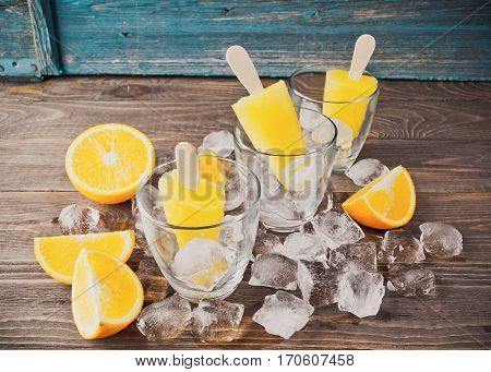 Summer Popsicles or orange juice frozen on a stick in glass glasses adorned with ice cubes and slices of ripe orange on a dark wooden background.The horizontal frame. Place for text.