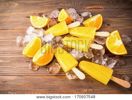 Homemade Popsicles or frozen orange juice on a stick decorated with ice cubes and slices of ripe orange on a dark wooden table. The view from the top.