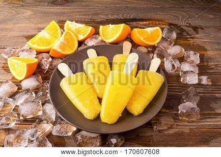 Homemade Popsicles or frozen orange juice on a stick decorated with ice cubes and slices of ripe orange on a dark wooden table. The view from the top