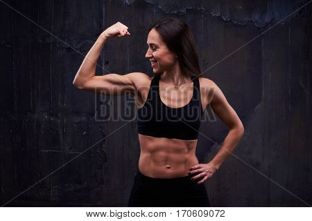 Close-up of cheerful woman in the studio, showing biceps. Woman with perfect biceps and triceps demonstrating muscles. The concept of sport and healthcare