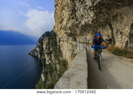 Mountain biking  man at sunrise over Lake Garda on path Sentiero della Ponale, Riva del Garda, Italy