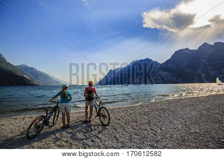 Mountain biking woman and young girl over Lake Garda.